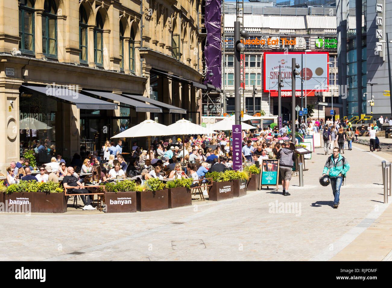 A summer day in Manchester city centre with many people sat eating and drinking outside Banyan Bar and other restaurants and bars of The Triangle, for Stock Photo