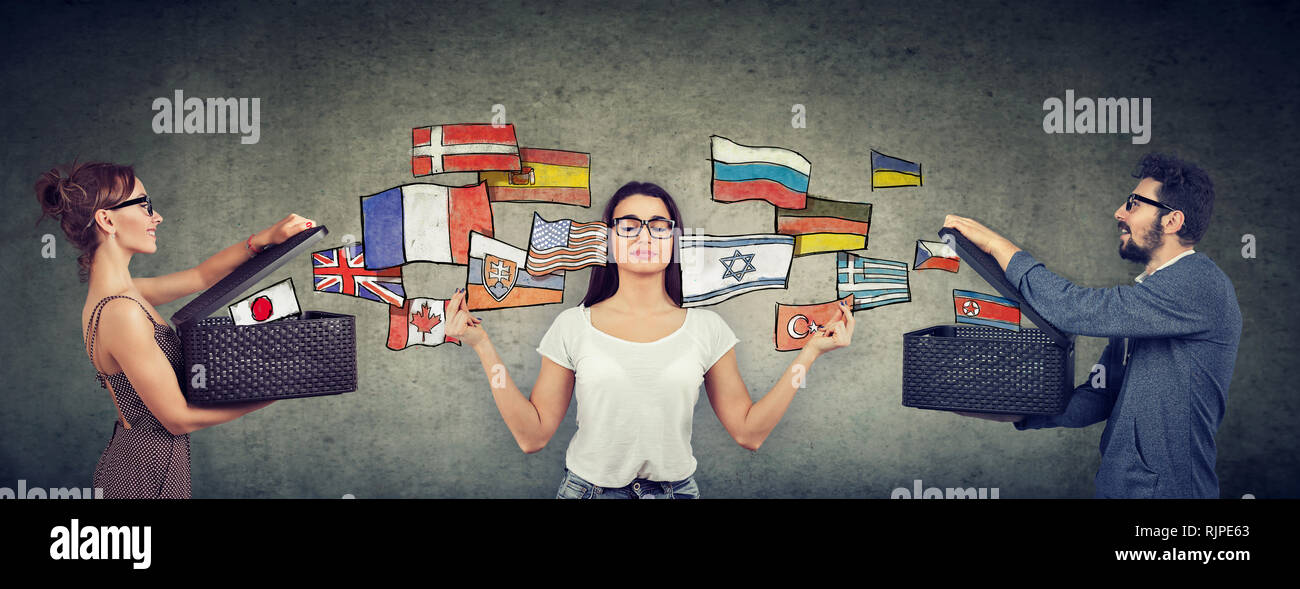 Young girl meditating learning different languages being exposed to different cultures by man and woman with opened boxes and international flags flyi - Stock Image