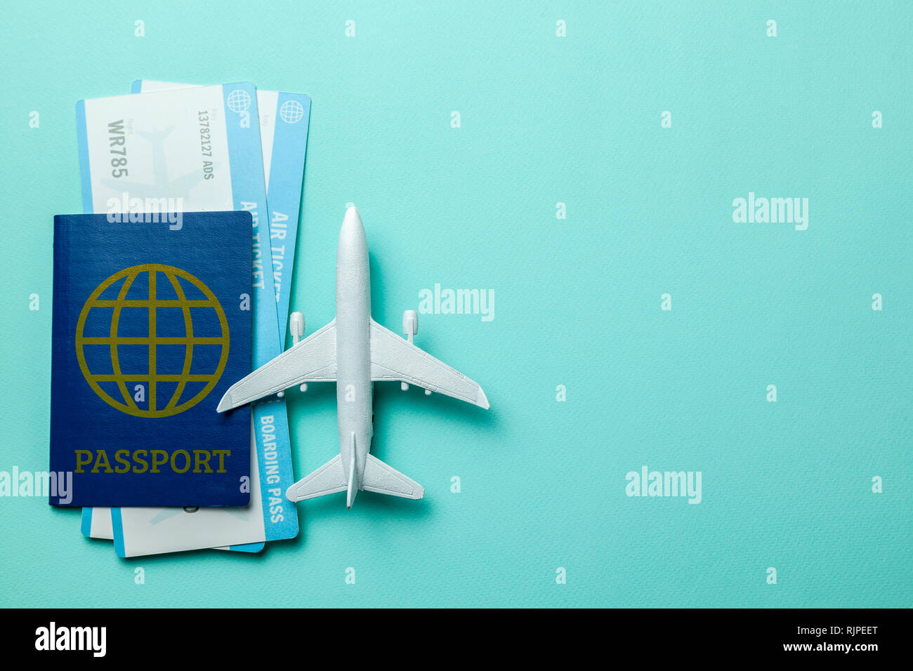 Tickets for plane and passport with model of passenger plane on green mint background. Copy space for text Stock Photo