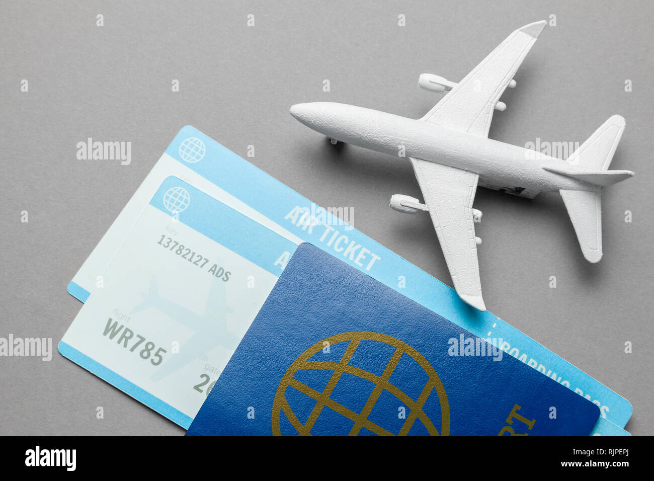 Tickets for plane and passport with model of passenger plane on gray background Stock Photo