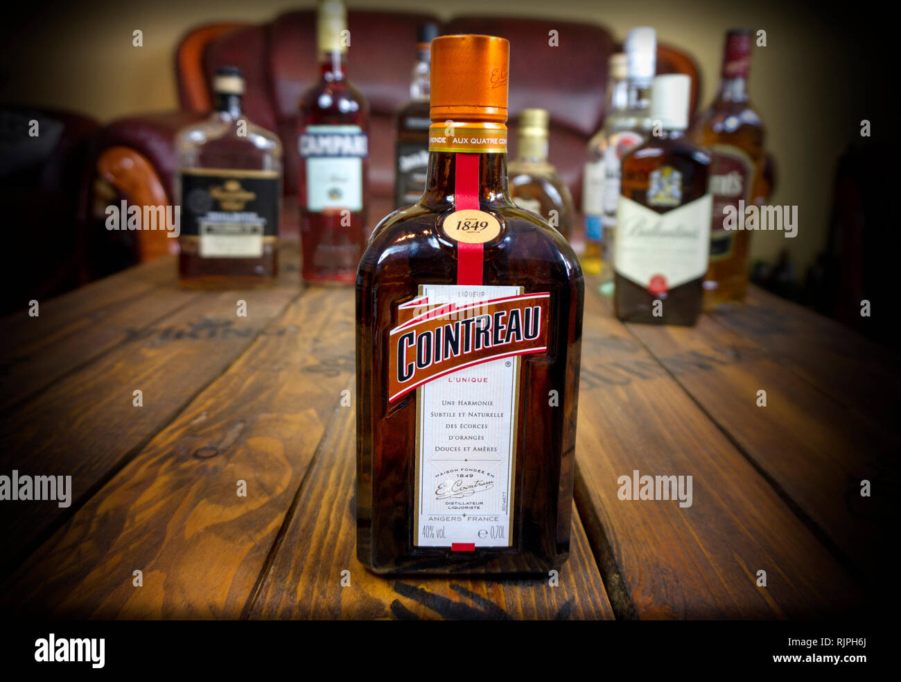 Alcoholic french ligueur cointreau outstanding on wooden table with other alcoholic beverages illustrative editorial - Stock Image
