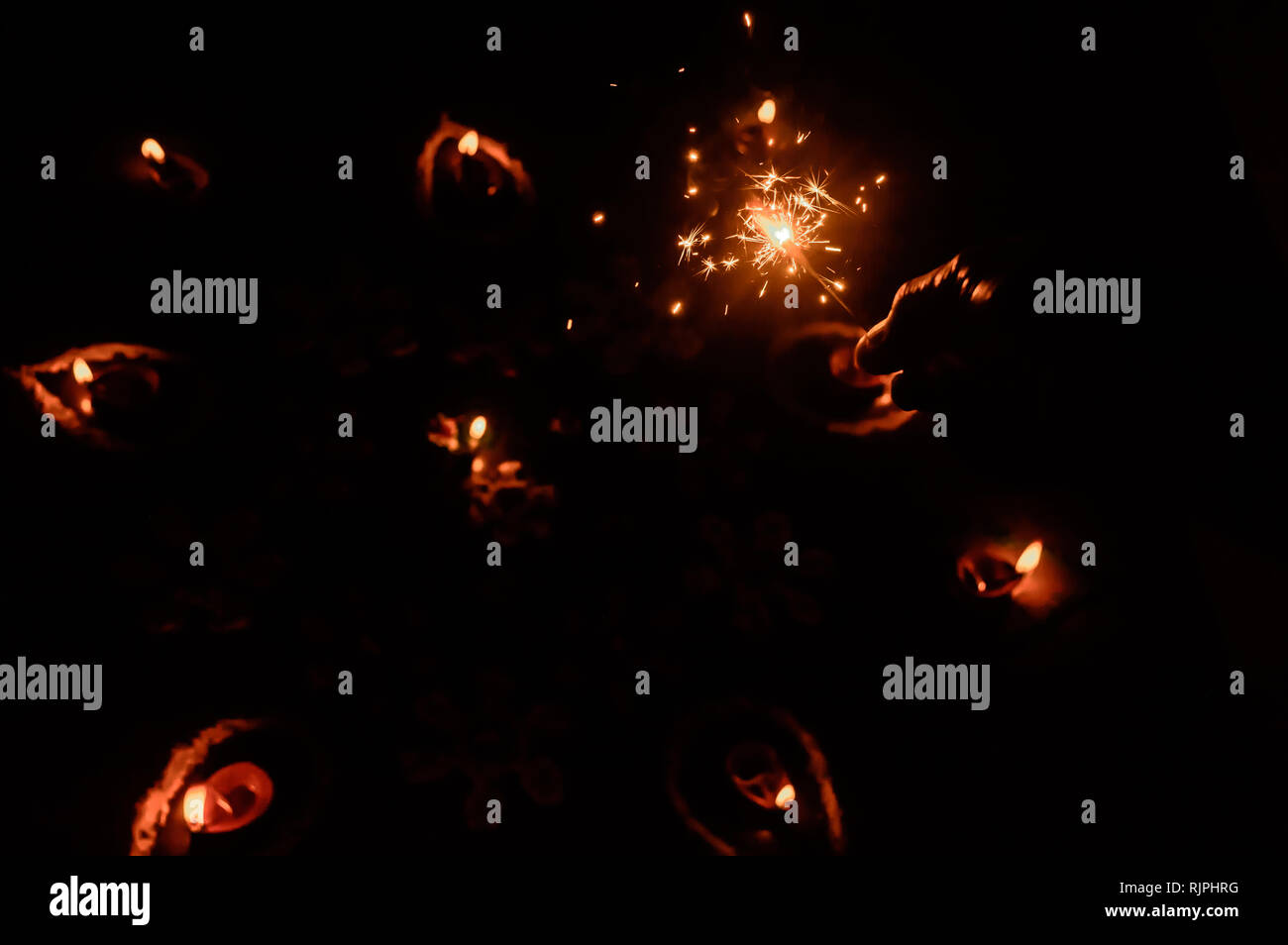 A burning Sparklers on hand over Diya-oil Lamps lit with real red flame in festival season of Diwali on black background. Removing darkness concept. S - Stock Image