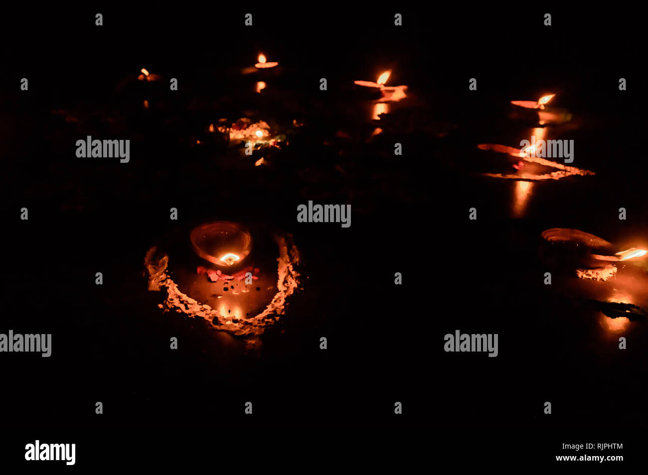 Diya- Lamps lit in festival season of Diwali. Group of burning oil lamp on black background. Candles lighting in darkness. Burning Candle with real re - Stock Image