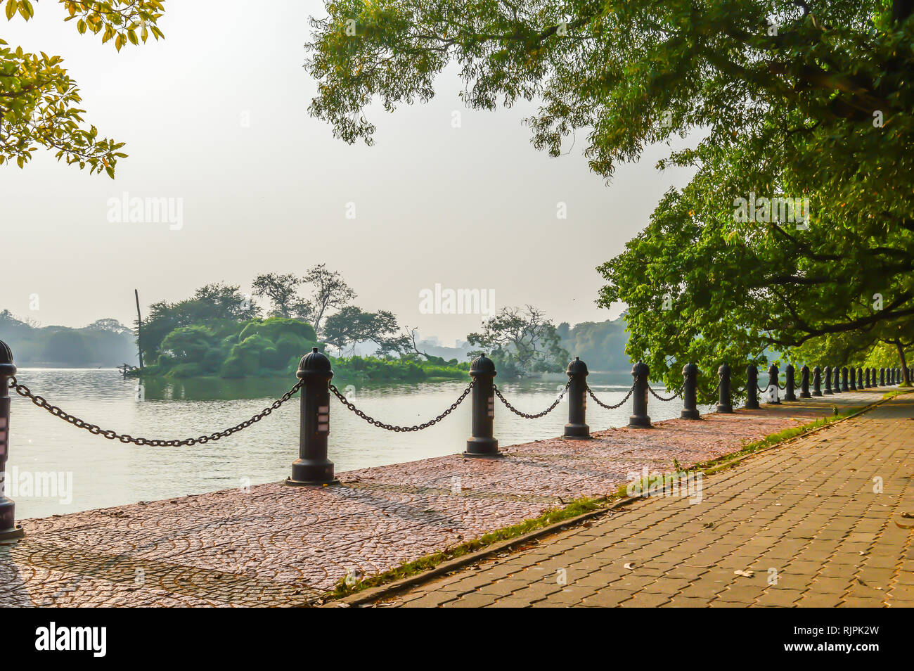 Front lawn for background with concrete pathway. black iron meta fence in background of lake. Garden landscape design. Footpath front or back yard gar - Stock Image