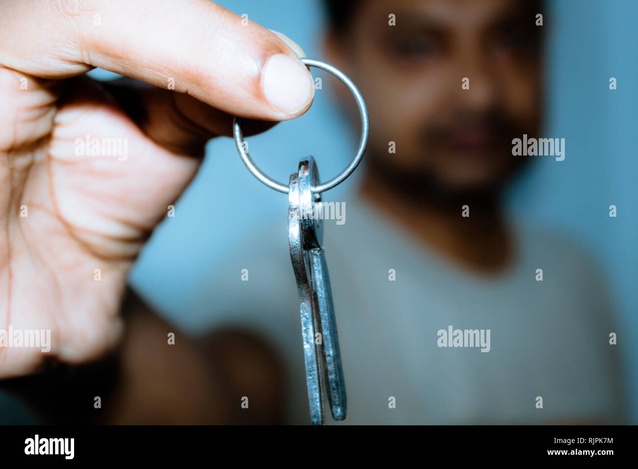 Business Men hand holding and showing a key ring. Real estate, moving in a new home or renting a property or Mortgage concept. Stock Photo