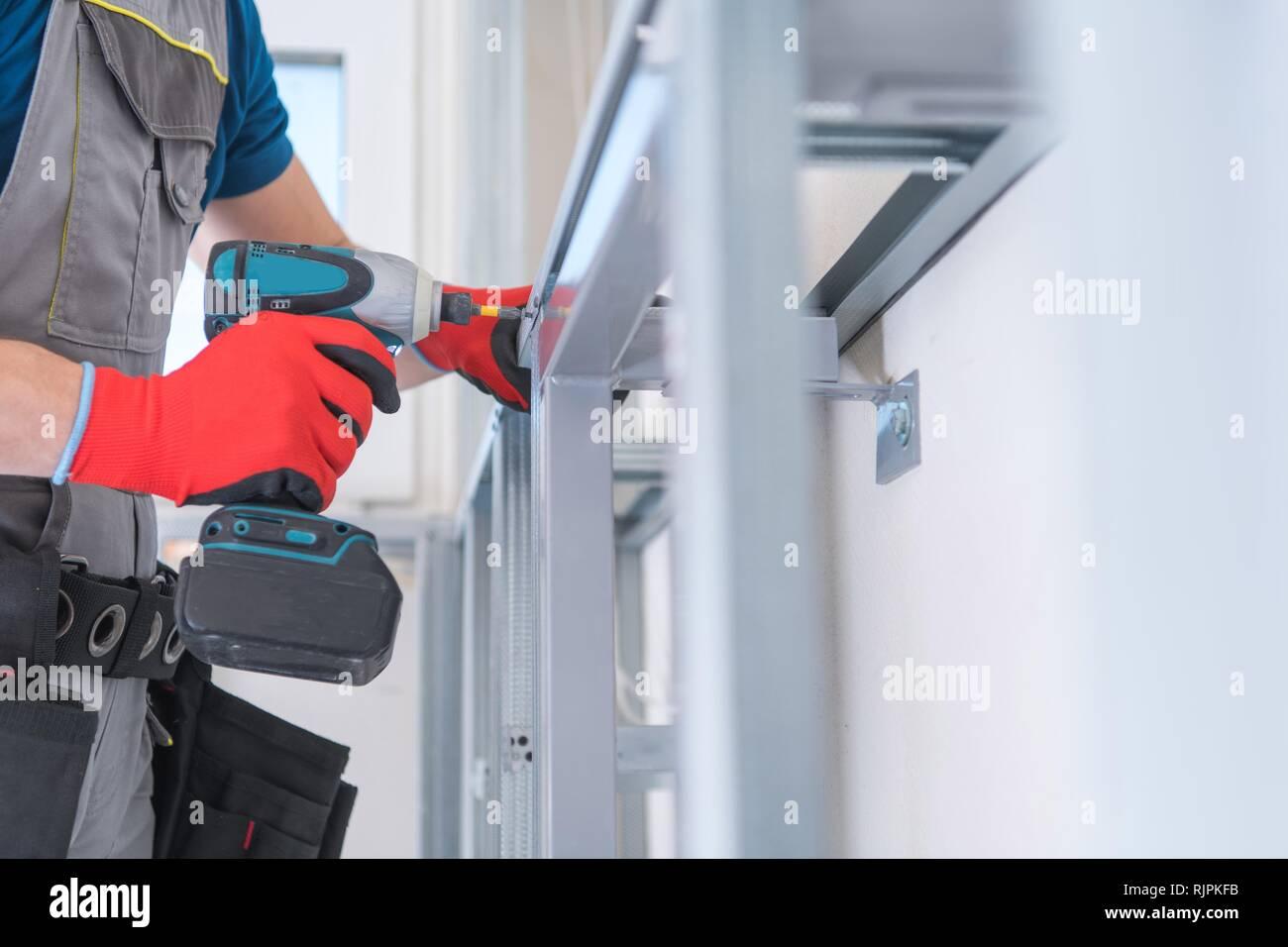 85663d07d35 Caucasian Worker Building Drywall Wall Frame by Attaching Aluminium Frames. Building  New Bathroom.