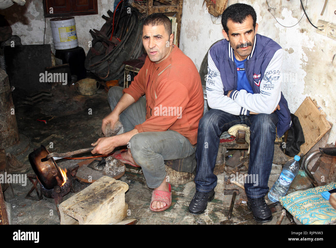 Metalworkers in their workshop at the Place el Seffarine, Medina of Fes el Bali, Fez, Morocco - Stock Image