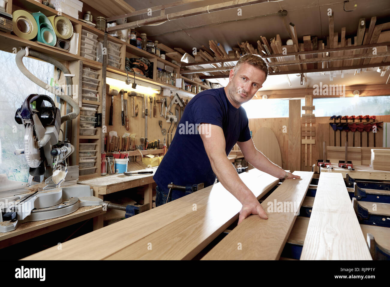 Craftsman preparing planks of wood in workshop - Stock Image