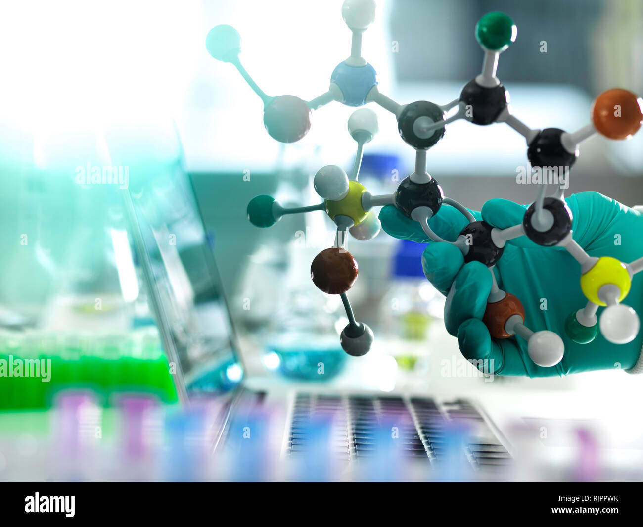 Chemistry research, researcher designing a chemical formula using a molecular model - Stock Image