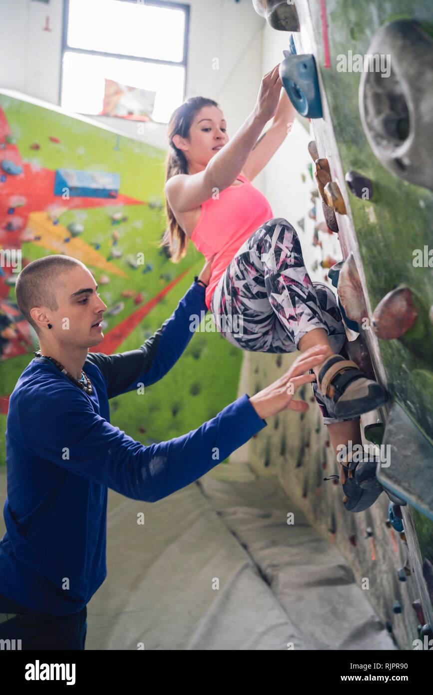 Climber guiding friend on climbing wall - Stock Image