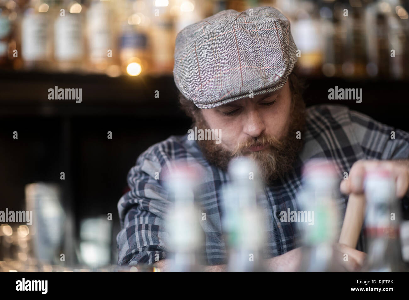 Barman working behind bar in traditional Irish public house - Stock Image