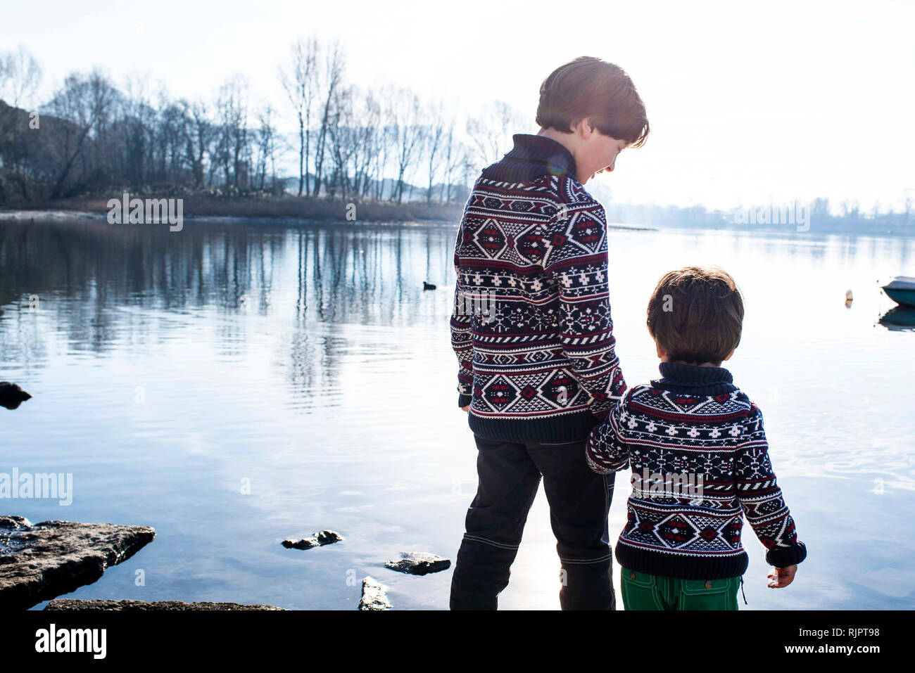 Boy and toddler brother in matching sweaters standing on lakeside, Lake Como, Lecco, Lombardy, Italy - Stock Image