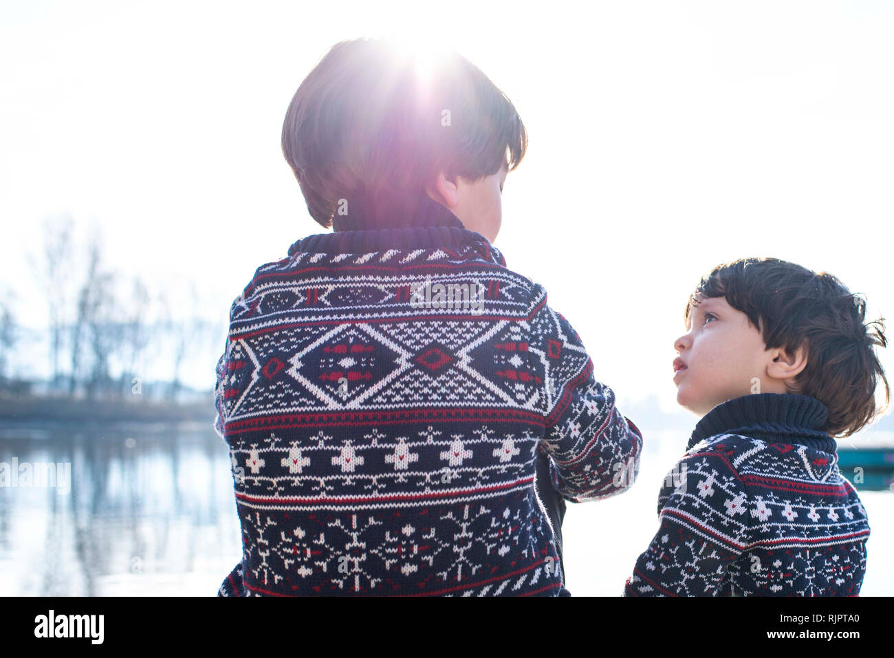 Boy and toddler brother in matching sweaters talking on lakeside, Lake Como, Lecco, Lombardy, Italy - Stock Image