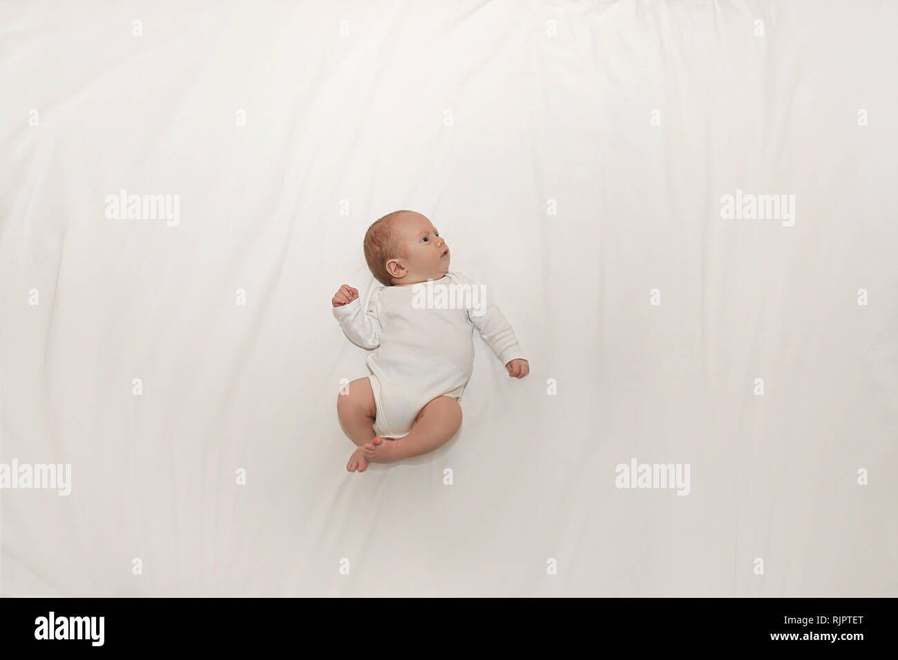 Tiny baby on spacious bed - Stock Image