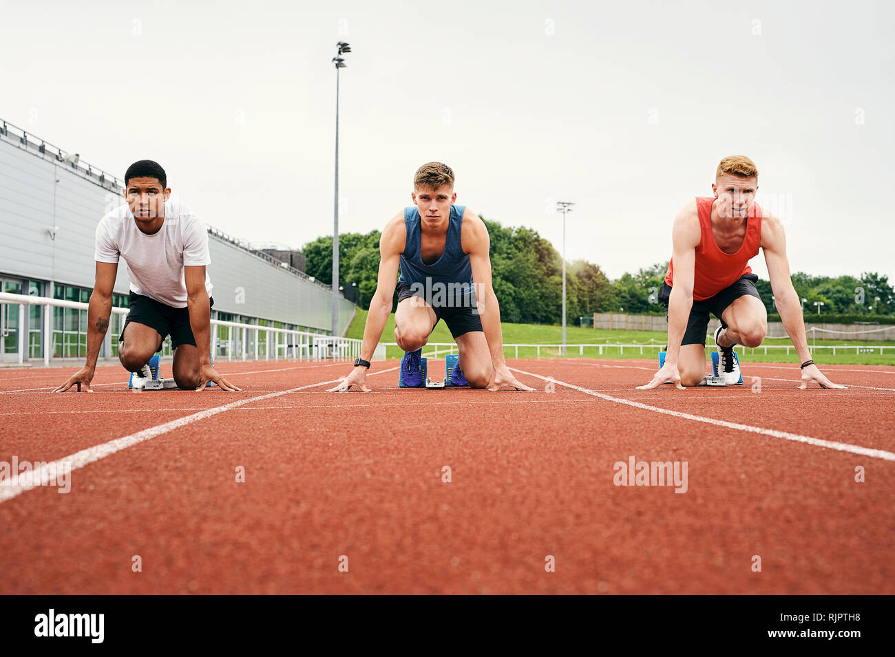 Runners at starting line on running track - Stock Image