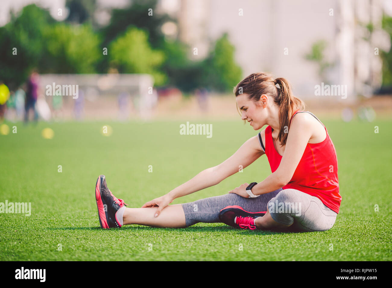 Theme sport and health. Young beautiful Caucasian woman sitting doing warm-up, warming up muscles, stretching green grass. Restoration and rest of - Stock Image