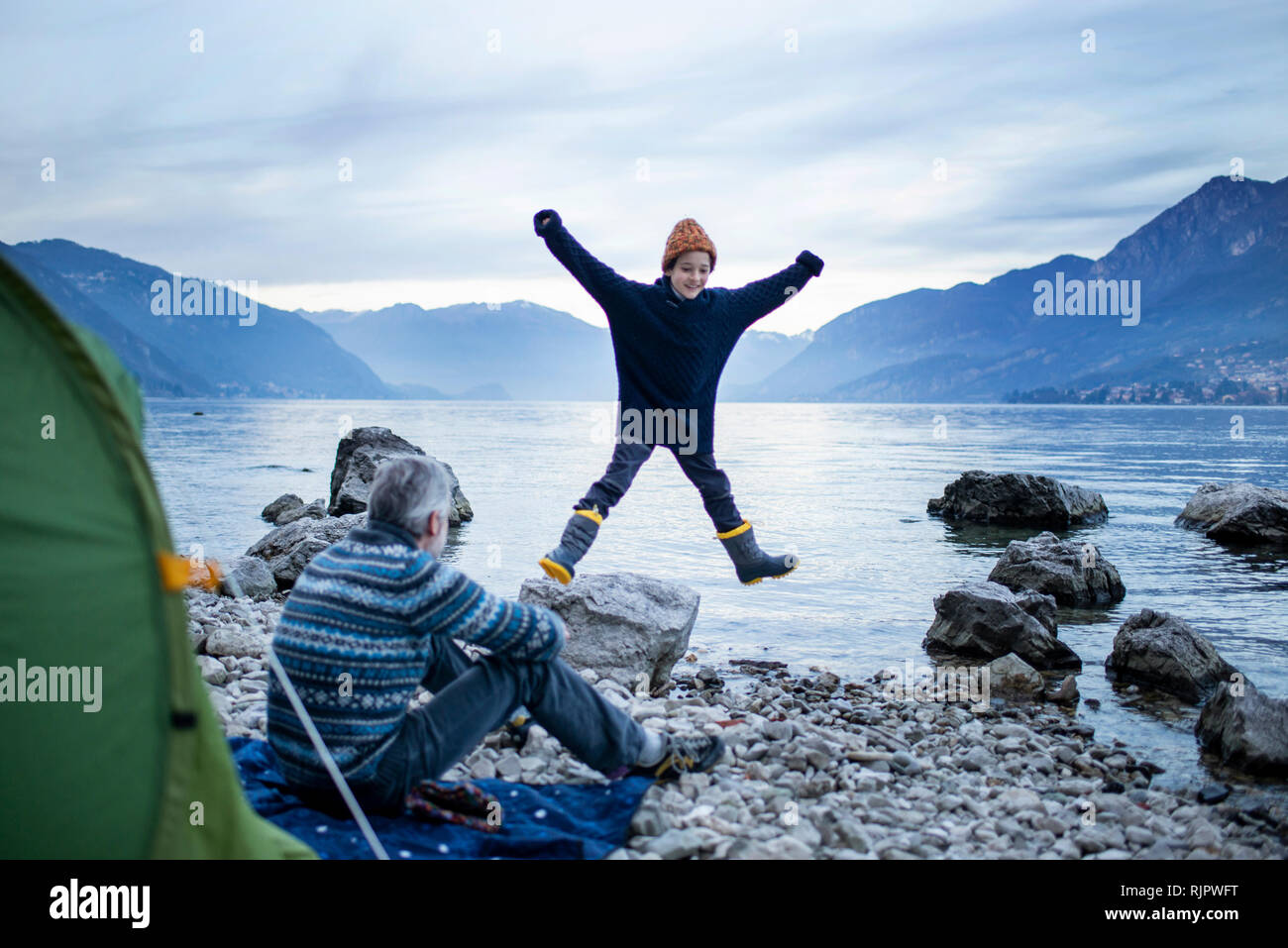 Father watching son doing star jump by lakeside, Onno, Lombardy, Italy - Stock Image