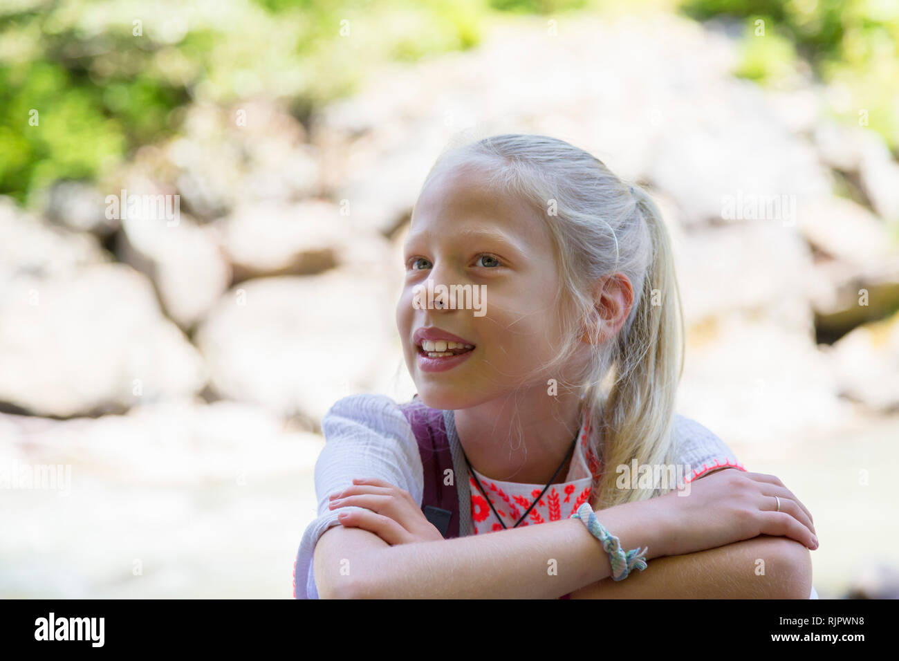 Blond haired girl with arms folded, head and shoulder portrait - Stock Image