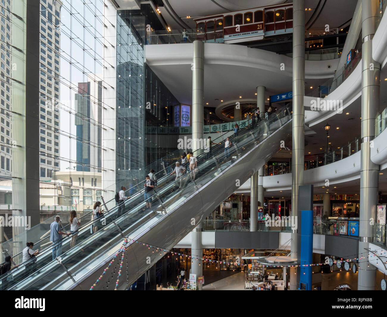The interior of a modern shopping precinct in Bangkok Thailand with escalators and people shopping - Stock Image