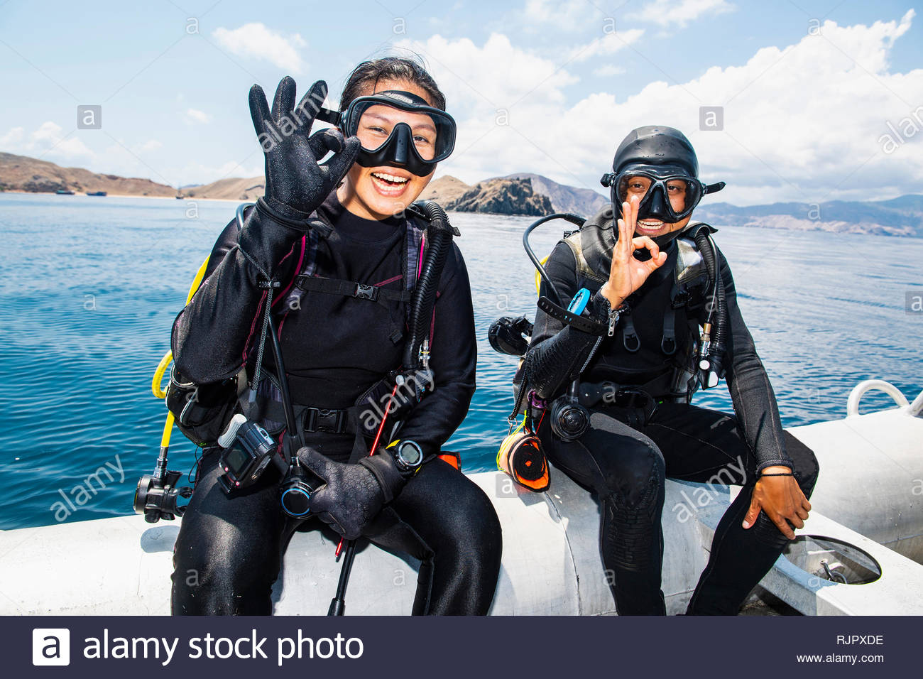 Two scuba divers about to submerge into sea - giving the 'all ok' hand signal,  Komodo Island, East Nusa Tenggara, Indonesia - Stock Image