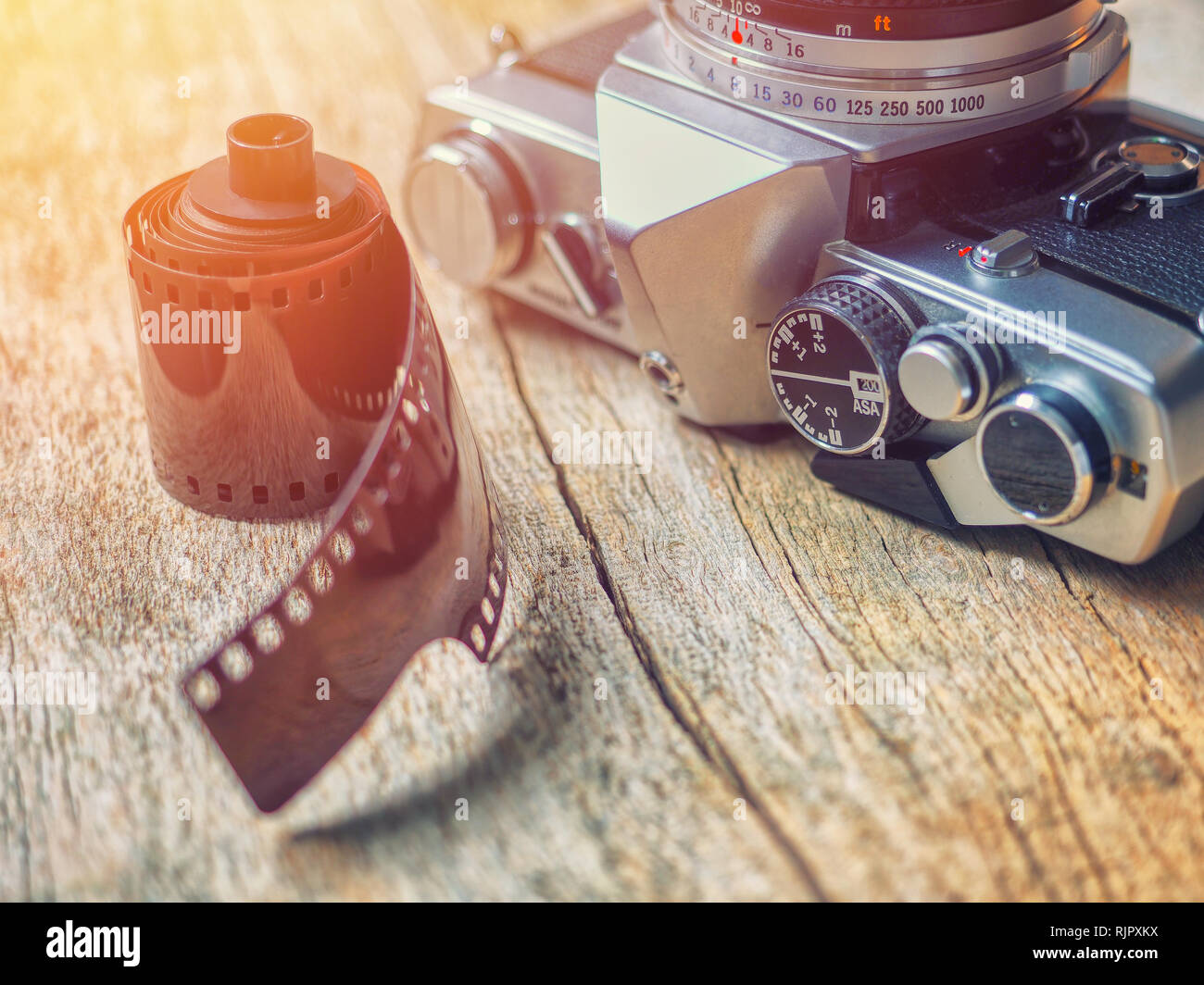 Close-up on old retro 35mm film SLR camera with photographic film resting on a wooden table - Stock Image