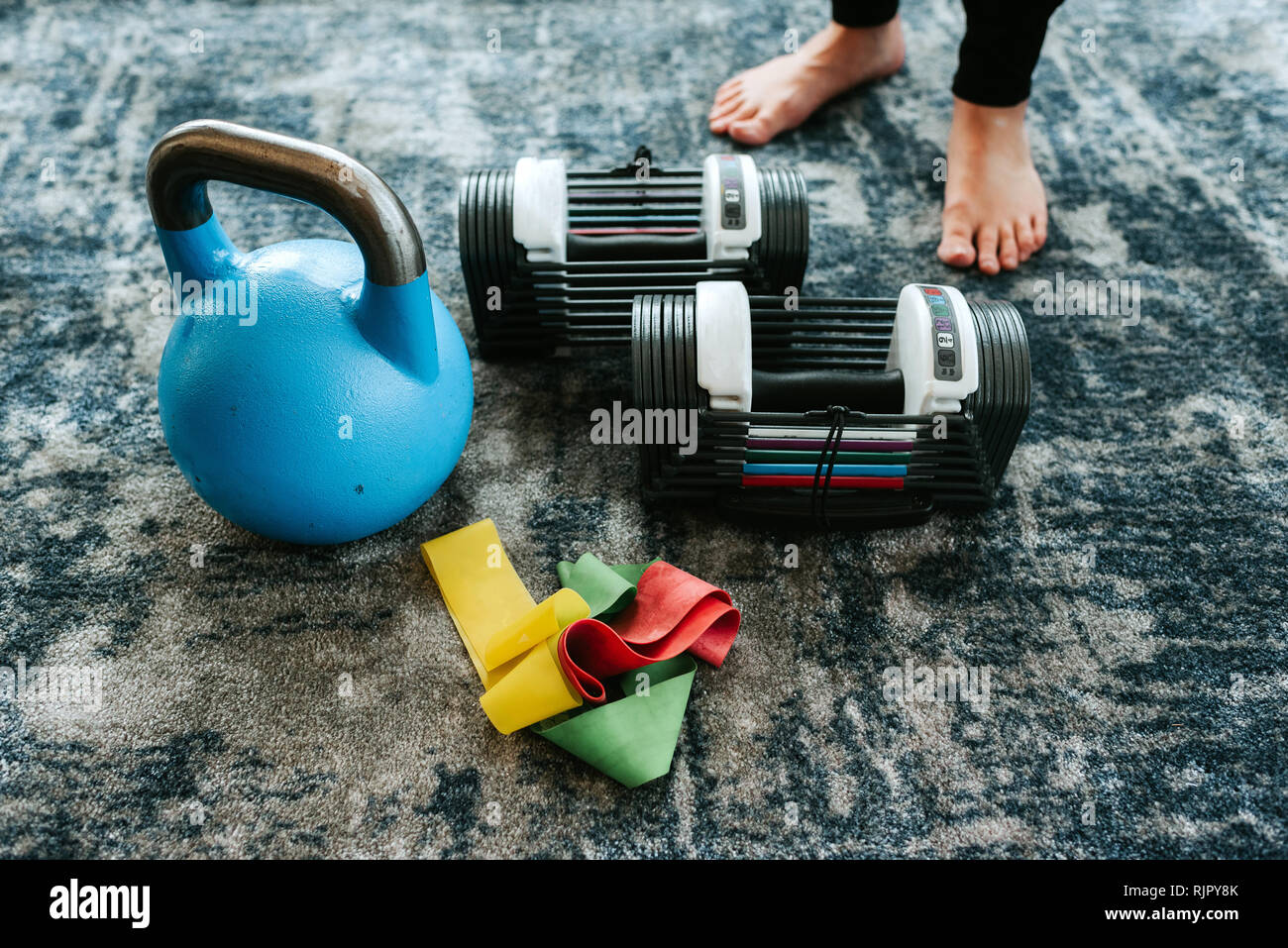 Kettle bell and assortment of exercise equipment by pair of feet - Stock Image
