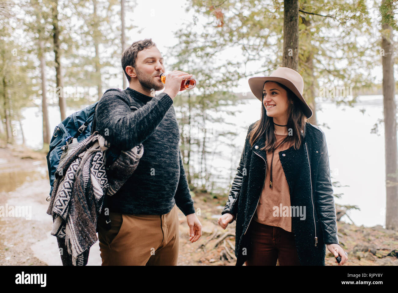 Couple quenching thirst during hike in forest, Tobermory, Canada - Stock Image