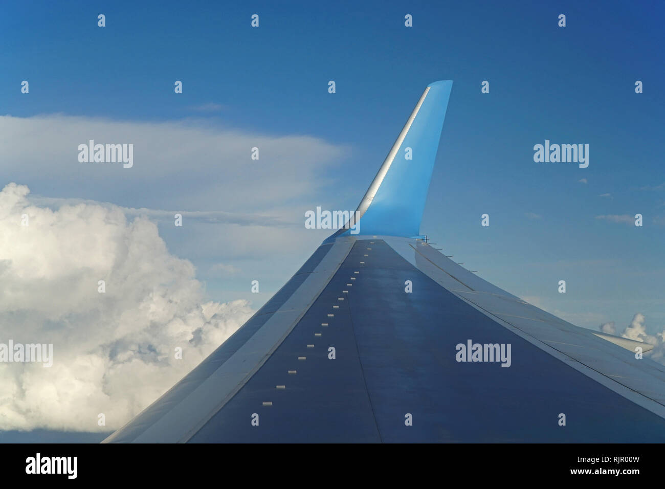 View of the wing of an aircraft in flight against a blue sky - Stock Image