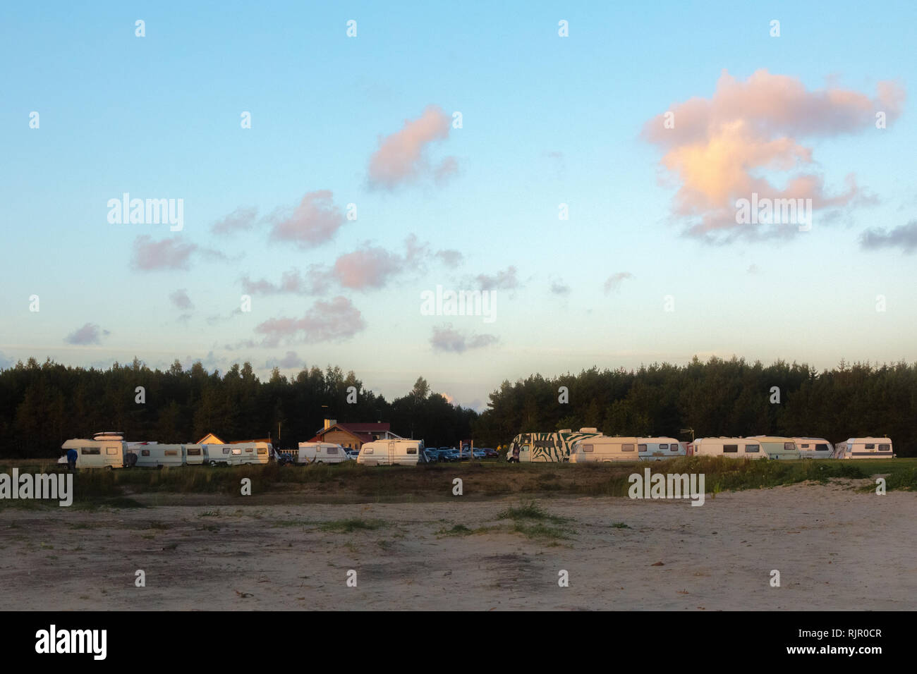 Scenic view of a caravan or trailer park next to woods in summer sunset with blue sky Stock Photo