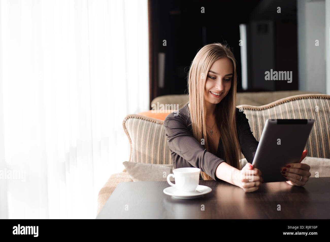 Beautiful pregnant woman using digital tablet at table in cafe - Stock Image