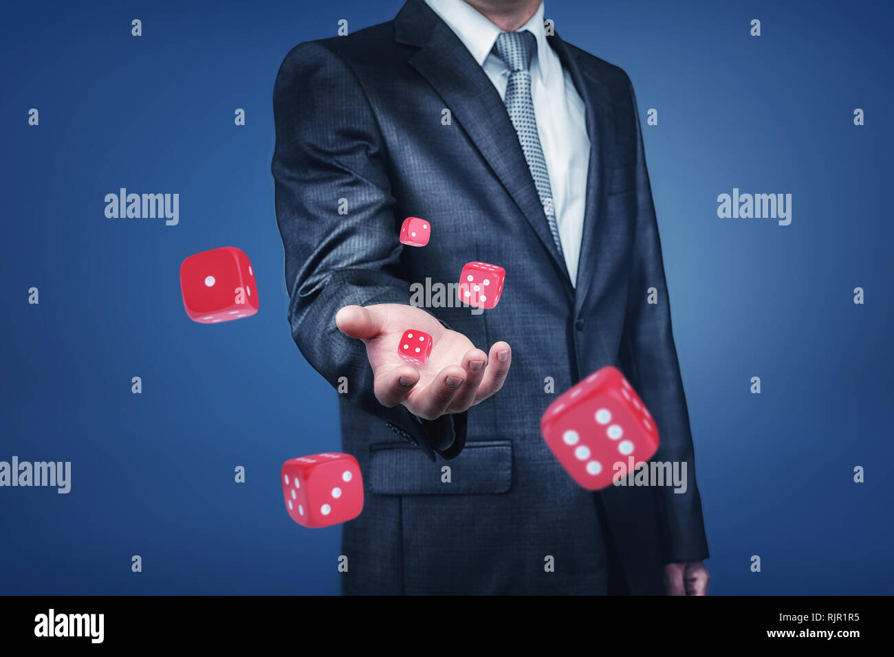 A businessman's arm throwing many red casino dice to the front in a close view. Playing business game. Winning and losing money. Career gambling. Stock Photo