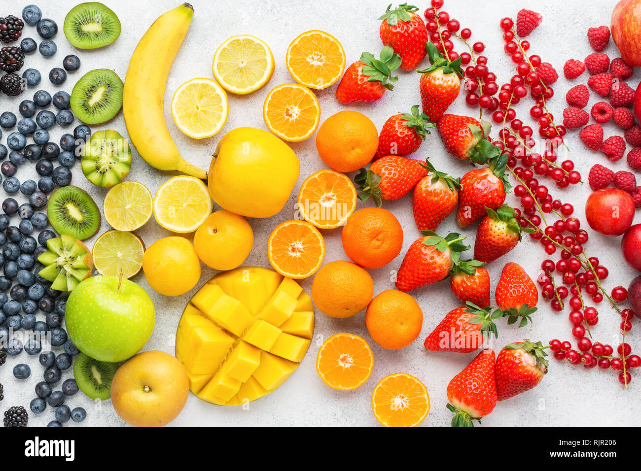 Colorful rainbow fruits berries background on white. Top view of strawberries blueberries cherries mango apple lemons oranges red currants plums - Stock Image