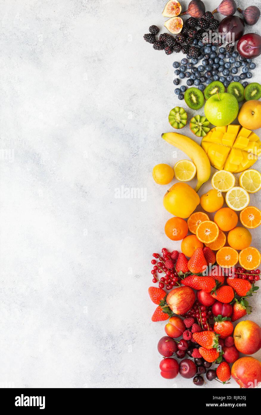 Rainbow fruits berries background on white. Top view of strawberries blueberries cherries mango apple lemons oranges red currants plums blackberries - Stock Image