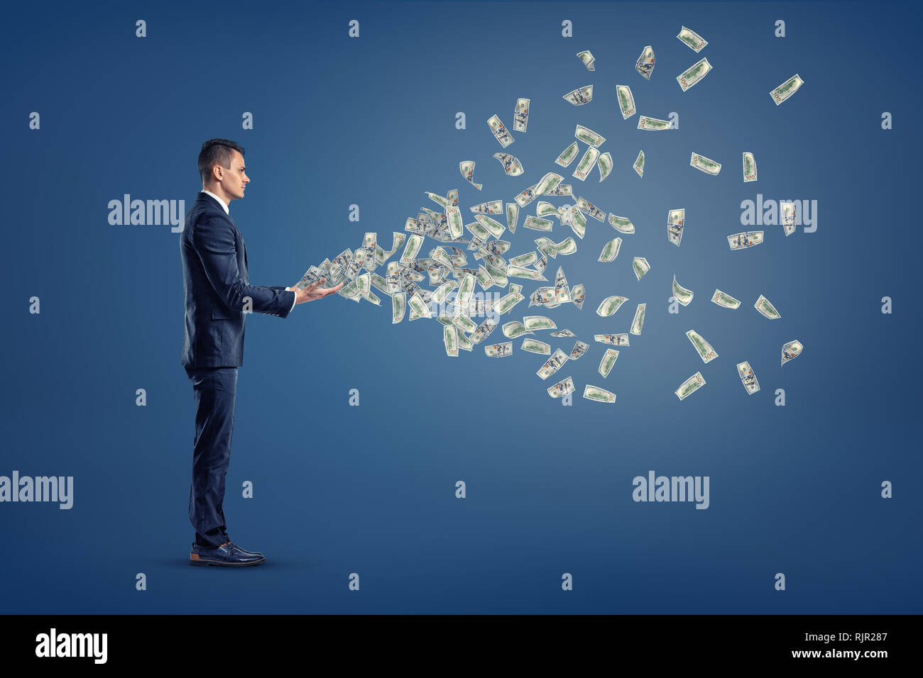 A single businessman stands in a side view with many USD dollar banknotes flying out from his hands. Spending earned money. Losing your income. Money  - Stock Image