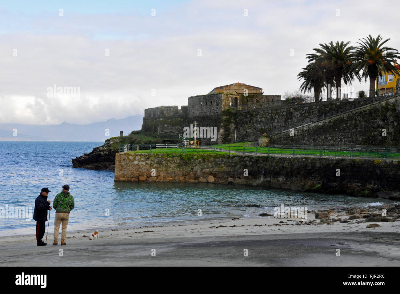 Two men chatting with Castle of San Carlos in the background. The castle is the final destination on the St.James Way. - Stock Image