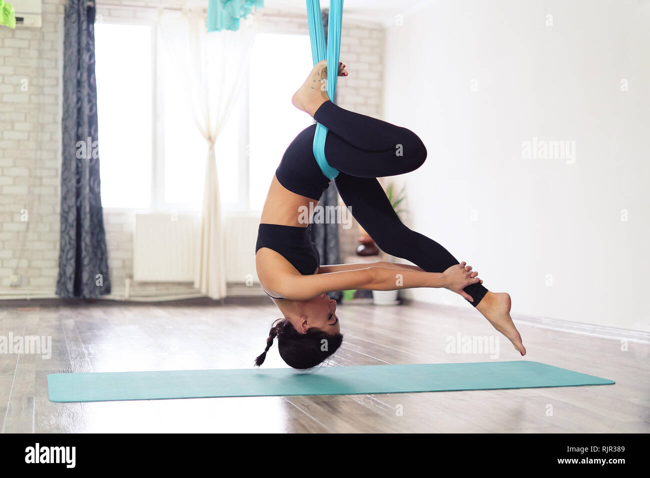 Full length of fit young woman doing antigravity yoga exercises in studio Stock Photo