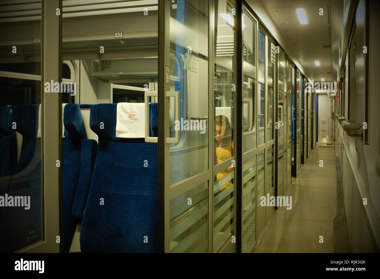 corridor on a train with separate compartments  on a railway passenger coach with one woman in a yellow dress. Stock Photo