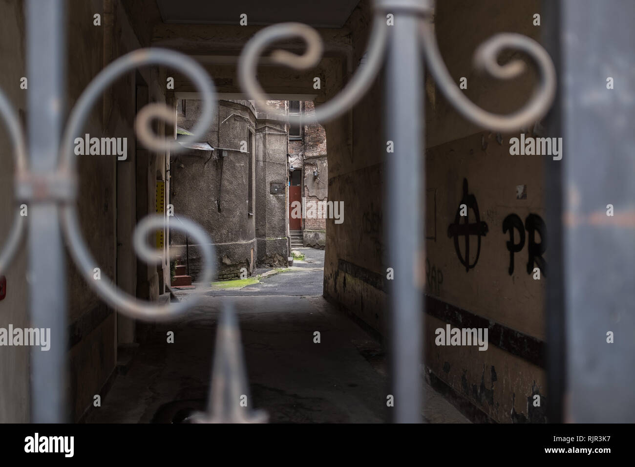 Alleyway leading into a courtyard in a ghetto tenement house in Warsaw seen through an iron gate Stock Photo
