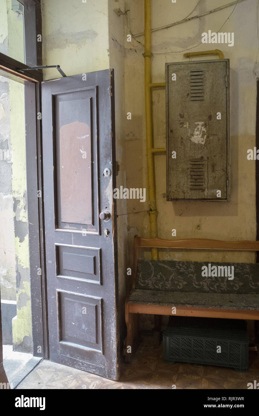 open wooden doorway with hallway into a tenement house with a bench Stock Photo