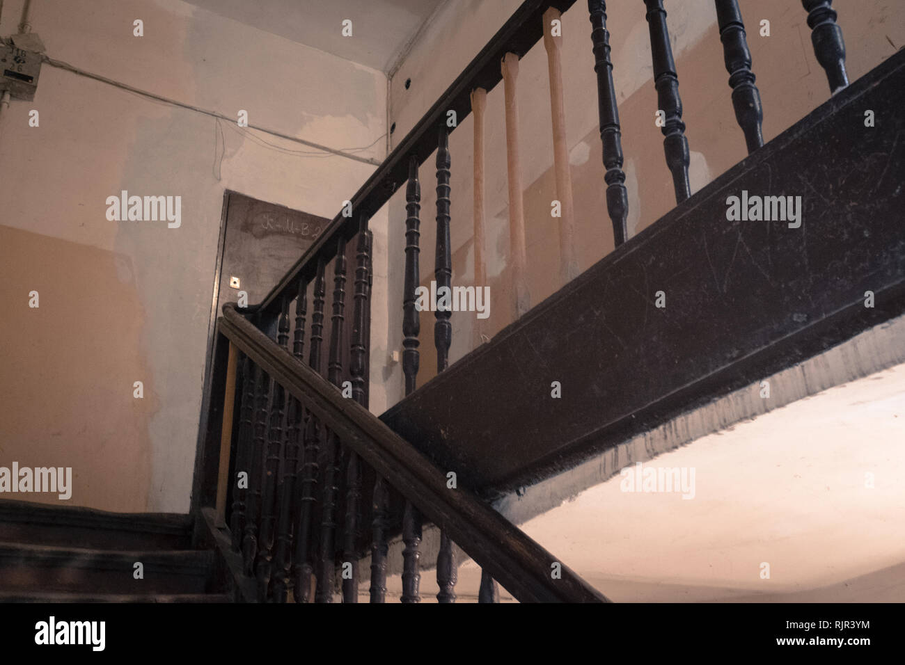 A staircase leading to a room in a building with new replacement spindles on the bannister Stock Photo