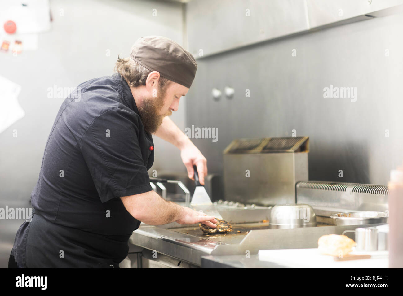 Fast food worker frying burger in commercial kitchen - Stock Image