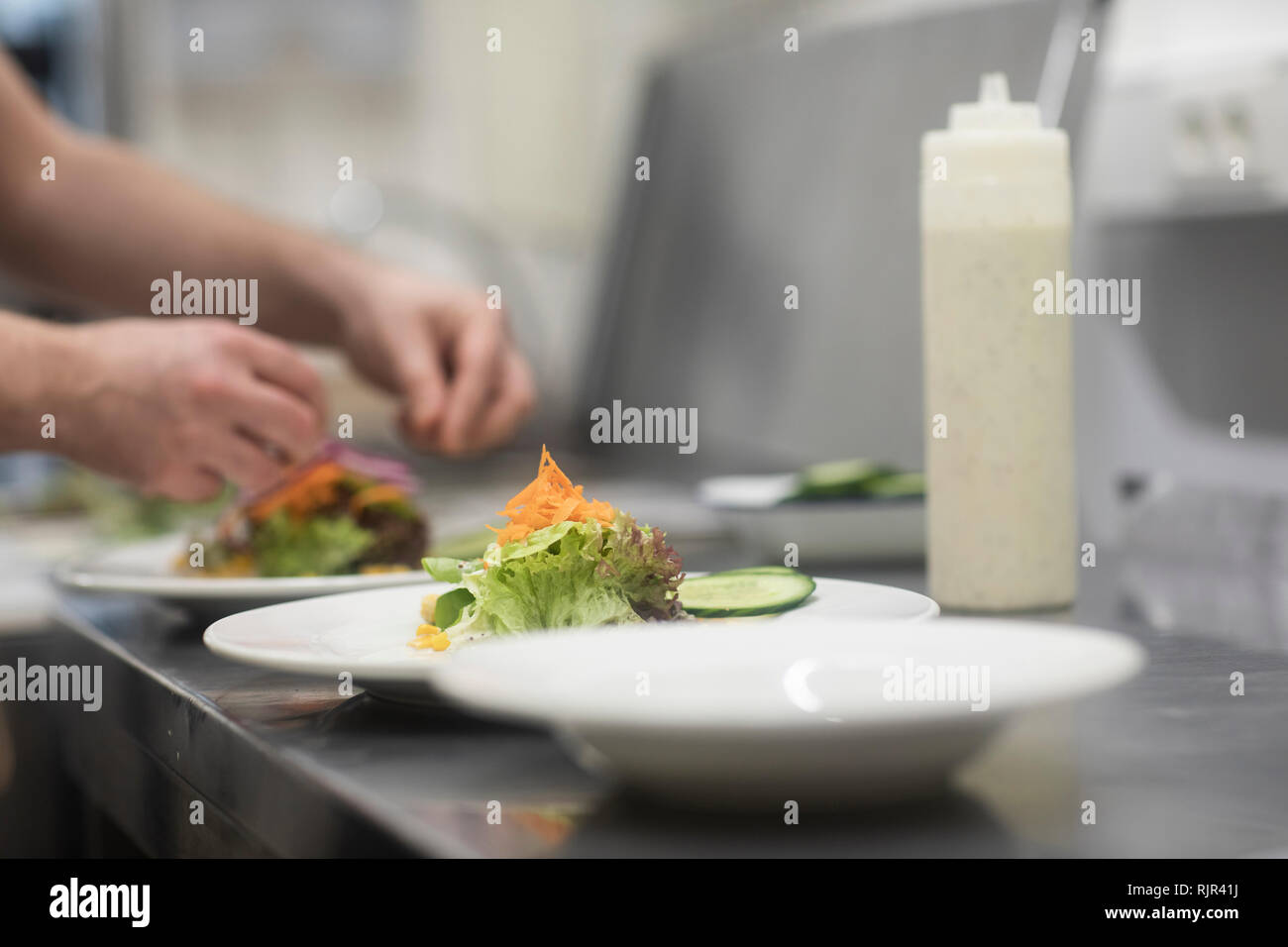 Fast food worker adding salad to hamburger in commercial kitchen, detail of hand - Stock Image