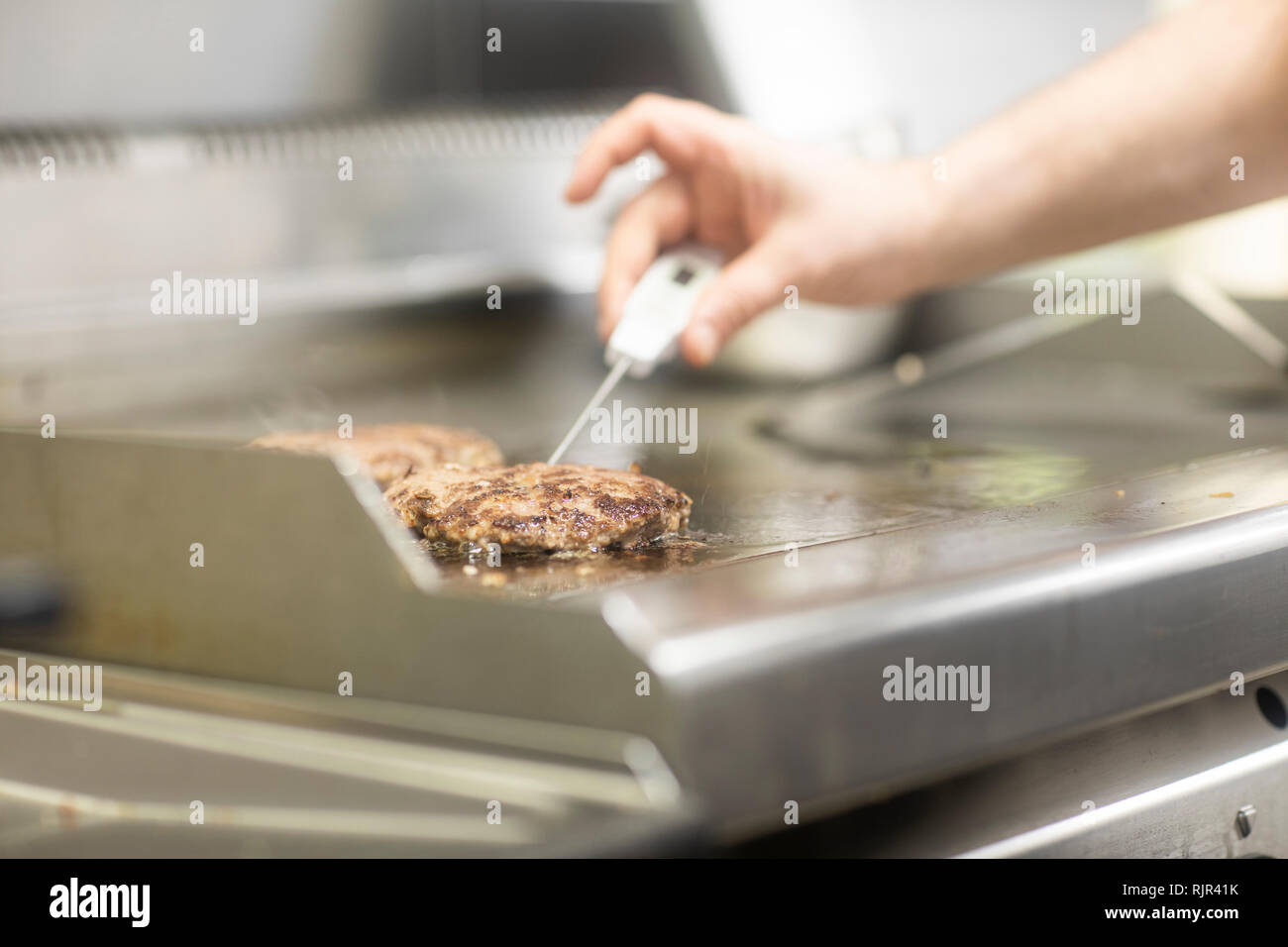 Fast food worker taking burger temperature in commercial kitchen, close up of hand - Stock Image