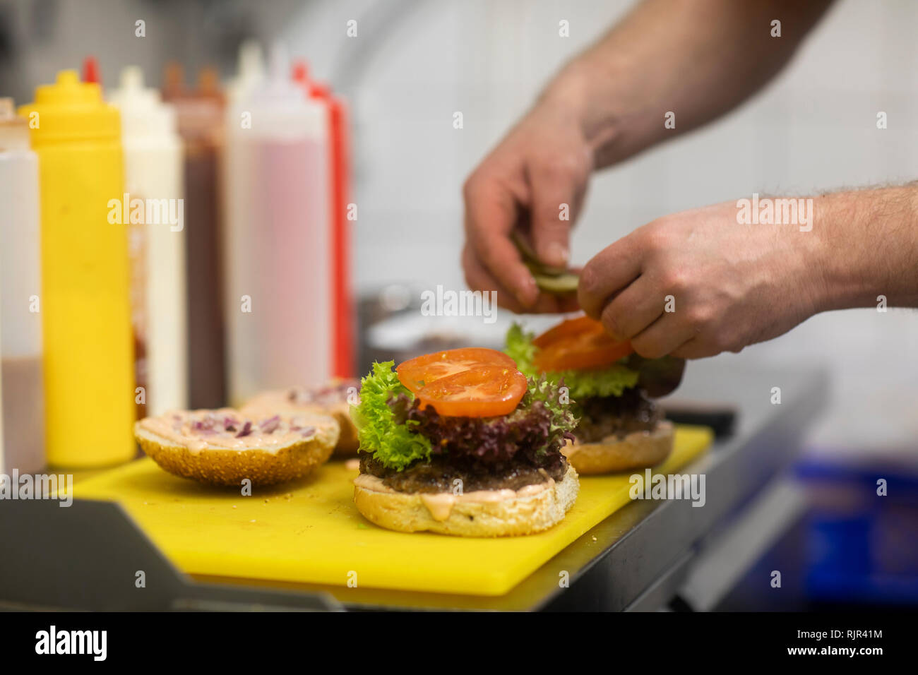 Fast food worker adding salad to hamburger in commercial kitchen, close up of hand - Stock Image