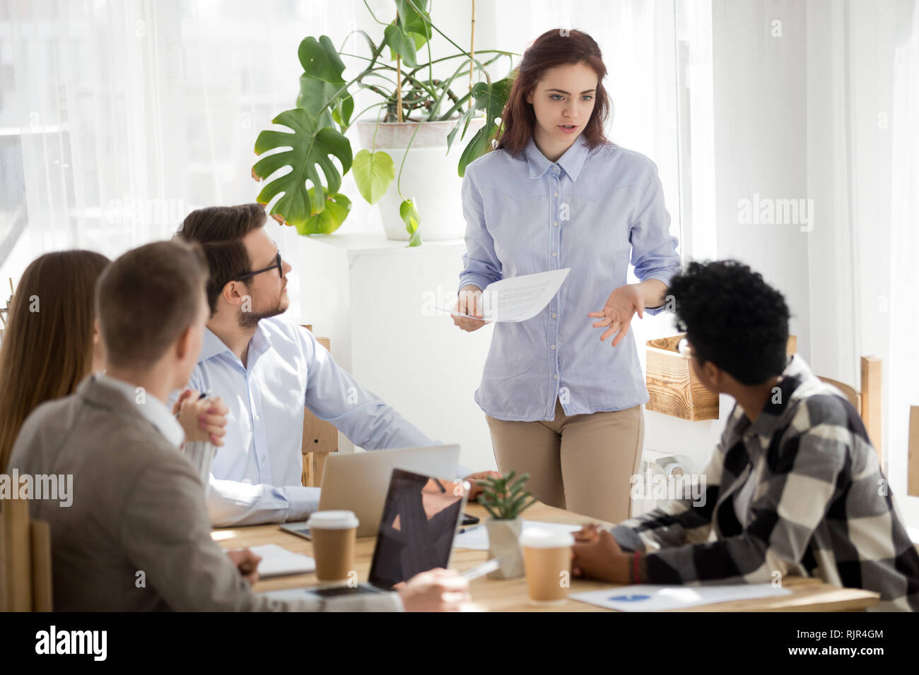 Caucasian employee having disagreement disputing with african coworker at meeting - Stock Image