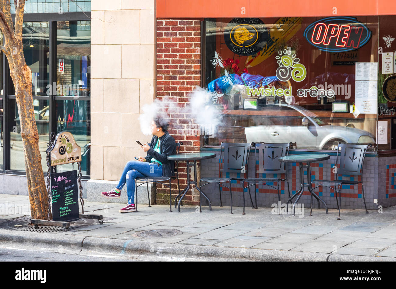 ASHEVILLE, NC, USA-2/3/19: Young woman sitting in front of restaurant, using a vaping device, creating smoke. - Stock Image