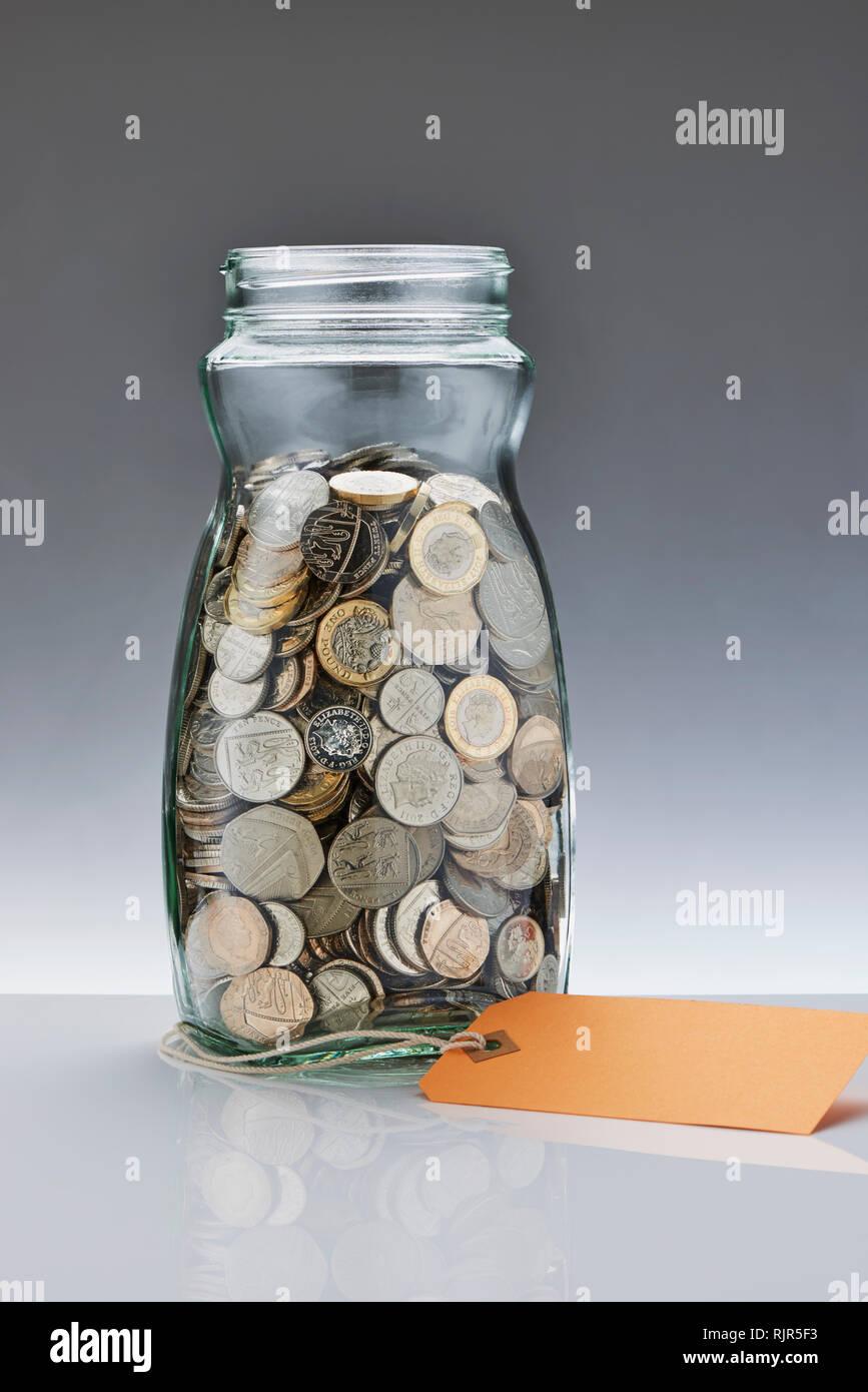 Glass Savings Jar with Pound Coins Stock Photo