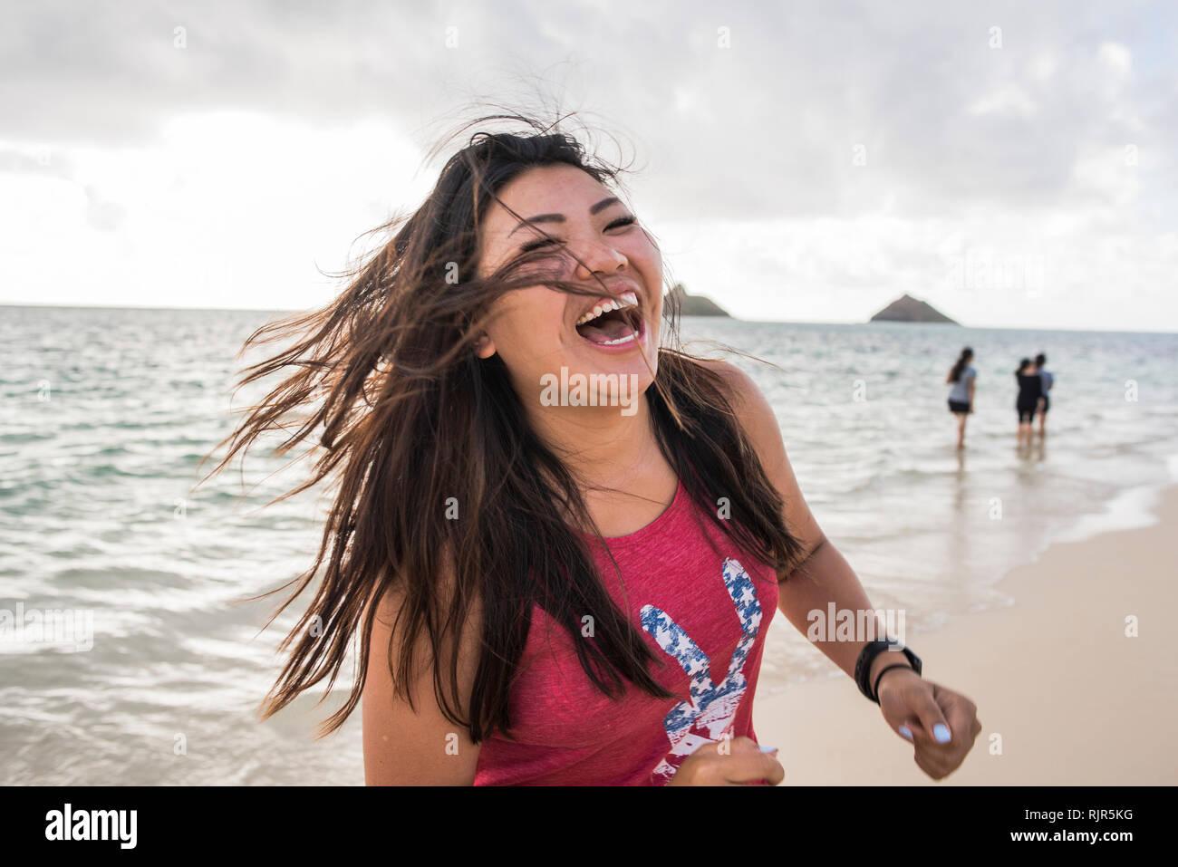 Woman swinging hair, Lanikai Beach, Oahu, Hawaii - Stock Image