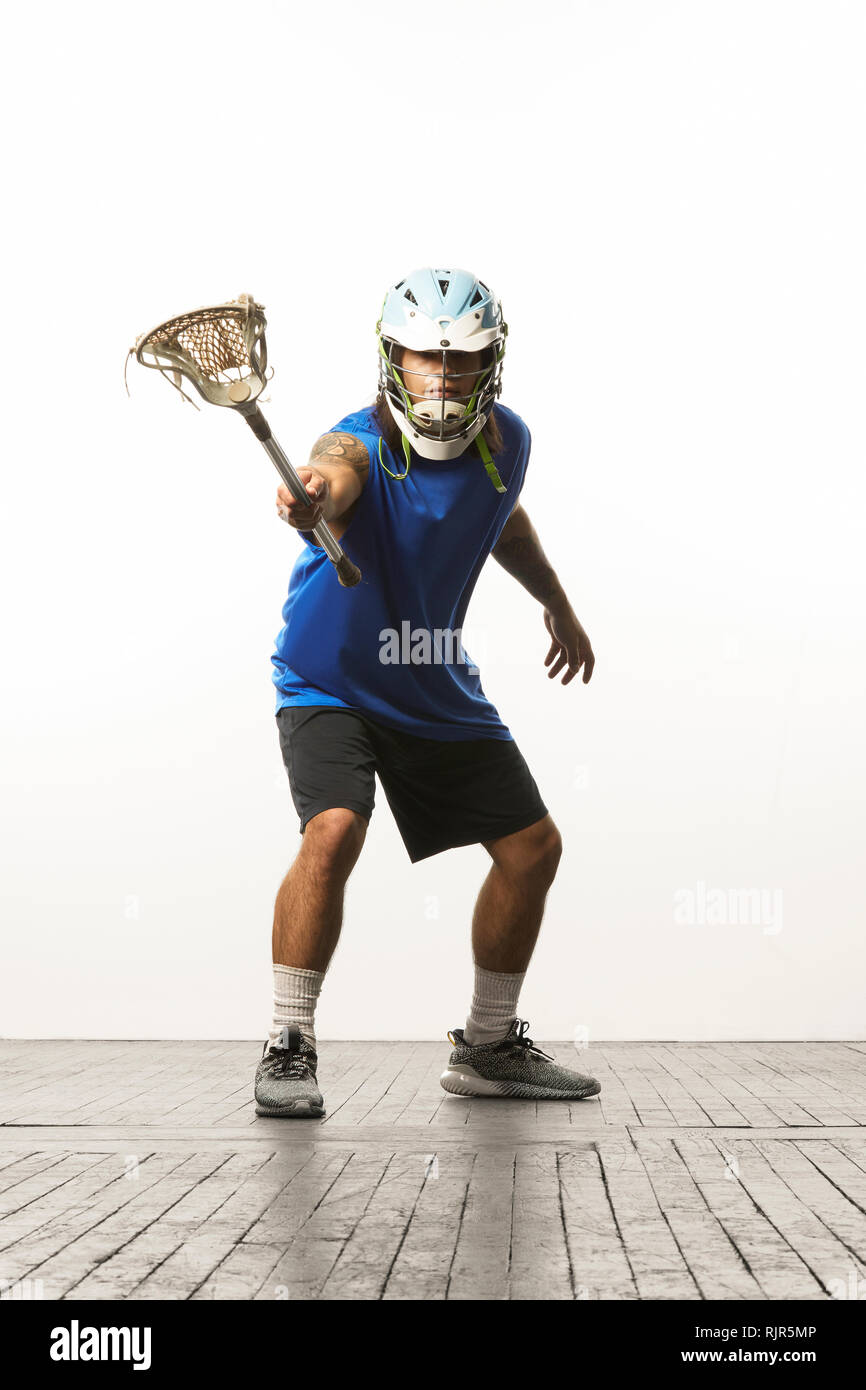 Man modelling lacrosse helmet and stick - Stock Image
