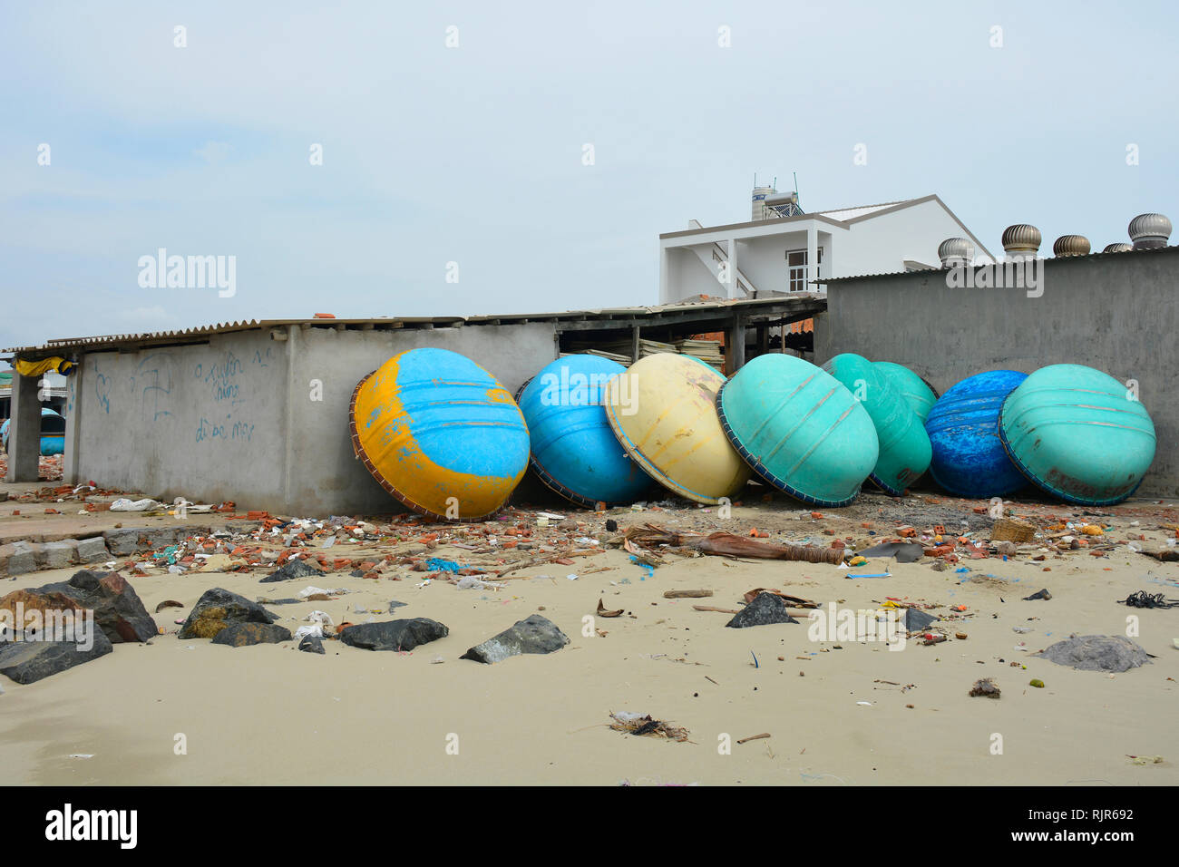 Mui Ne, Vietnam - December 27th 2017. Traditional fishing boats in Mui Ne Fishing Village propped up against a house. The beach is littered with rubbi Stock Photo